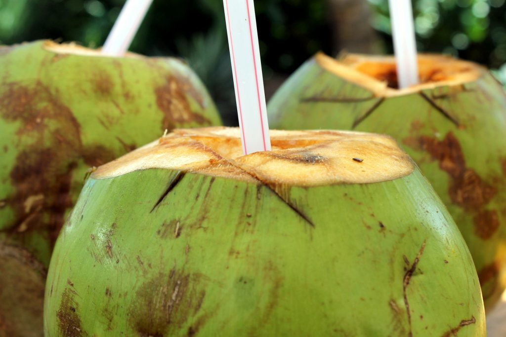 Coconuts cut with straw in them