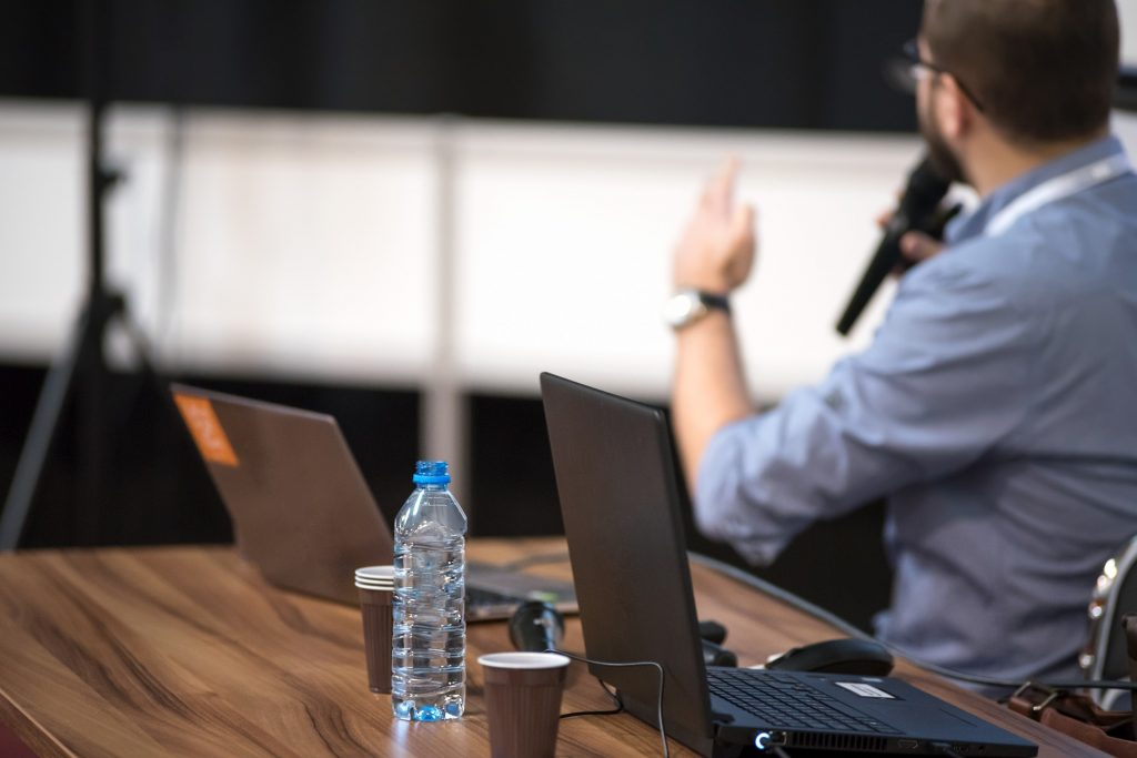 Table with laptops, coffee cups and water. Man speaking into a microphone in the background.