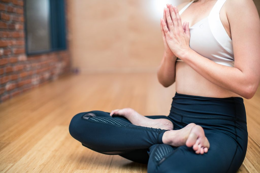 Woman sitting with legs crossed doing yoga on a wood floor.