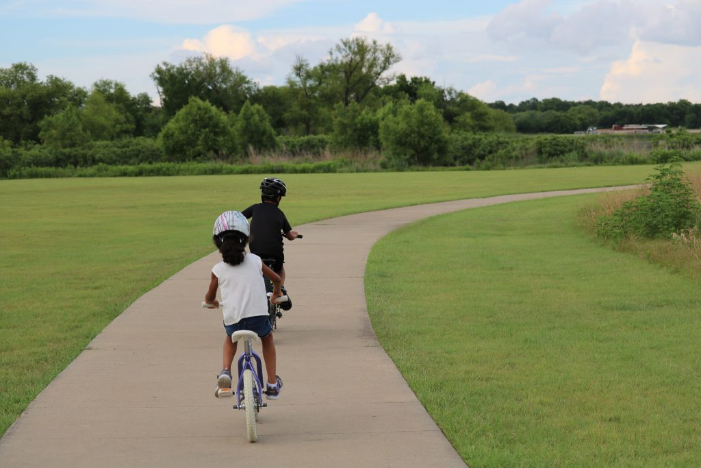 Two small children biking with helmets on paved path.
