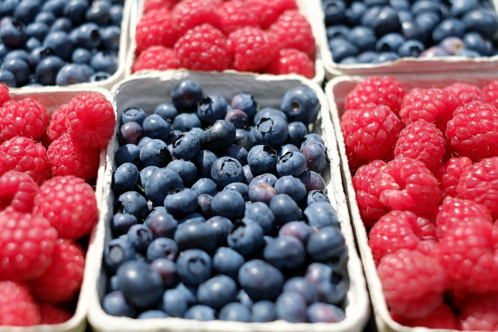 Cartons of blueberries and raspberries lined up together.