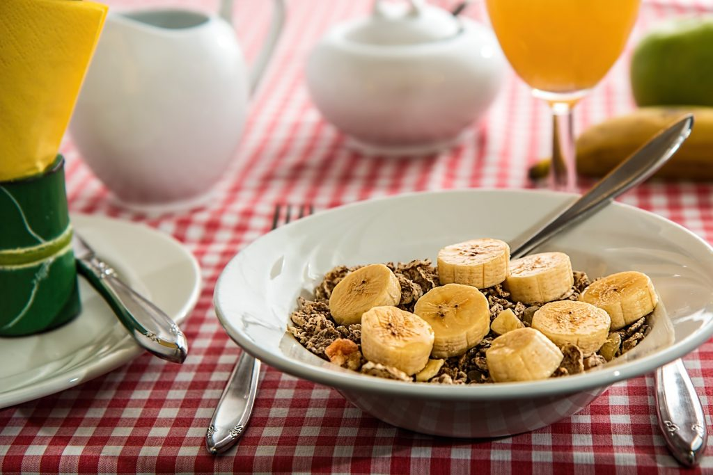 Cereal in bowl topped with cut bananas.