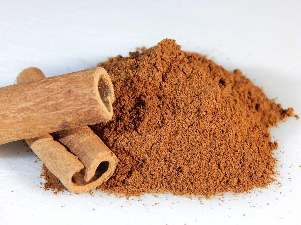 Ground cinnamon and whole cinnamon sticks on table.