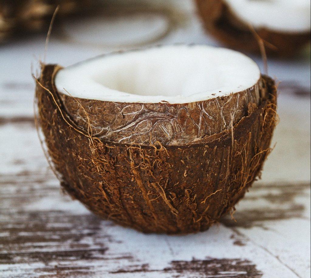 Fresh coconut, cut in half on table.