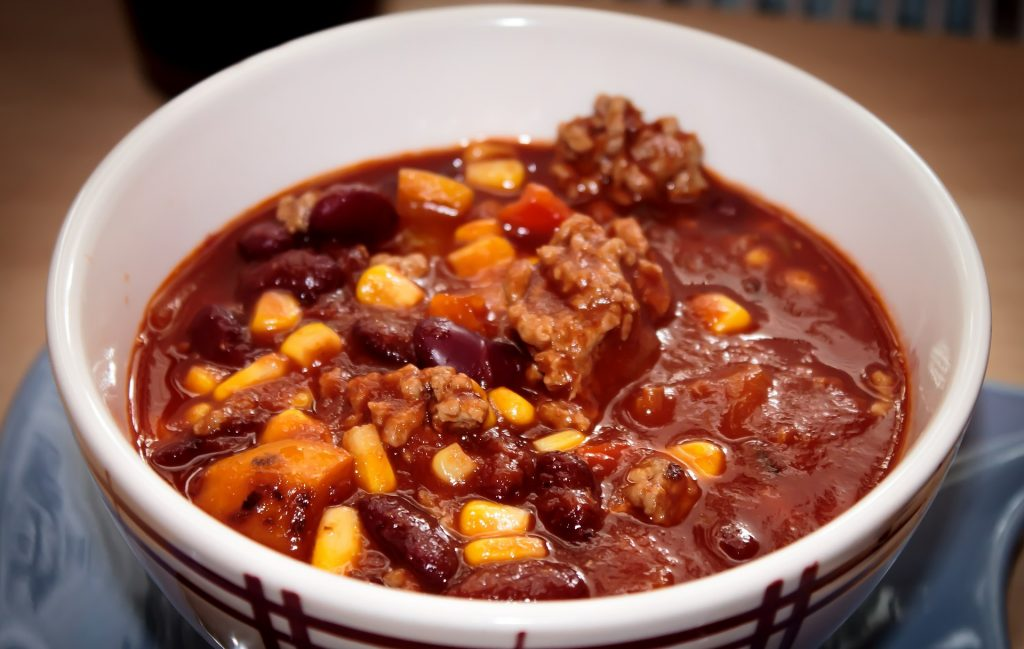 Chili with meat, beans, corn and vegetables in bowl.