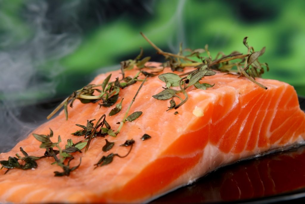 Raw salmon cooking with herbs on top.