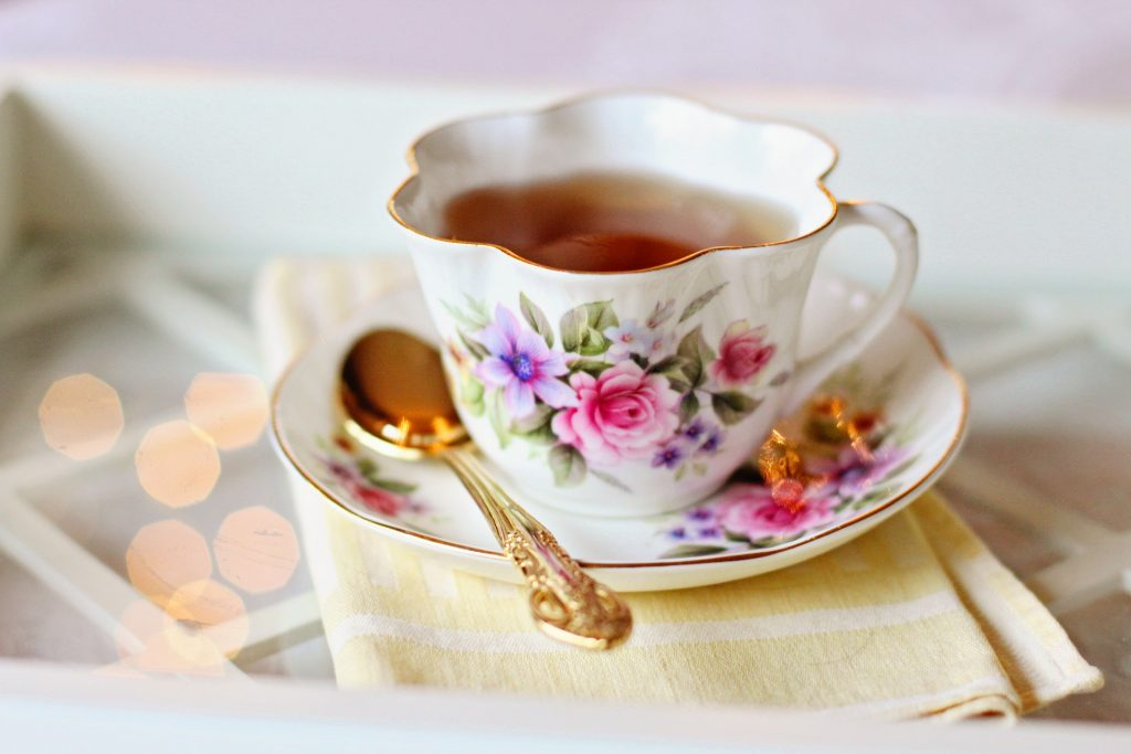 Cup of tea in teacup with flowers, on top of a matching saucer.