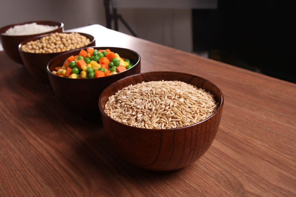 Bowl of grains, bowl of mixed vegetables, bowl of beans and bowl of rice on table.