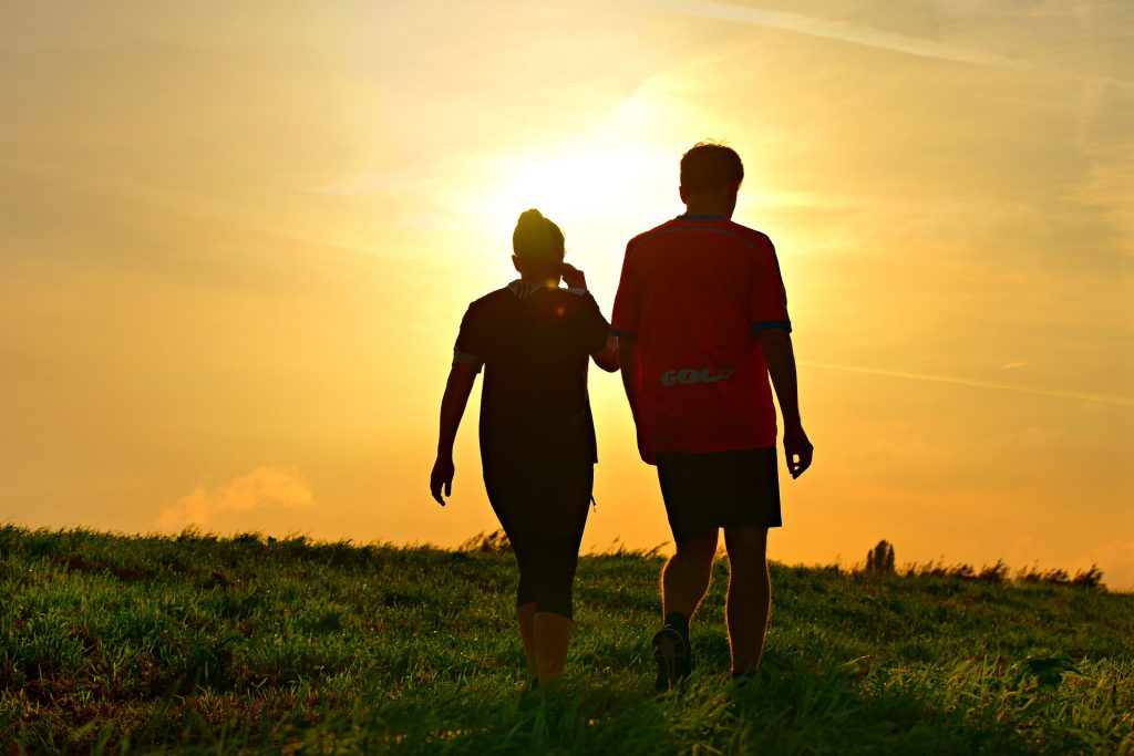 Man and women walking up a grassy hill and dusk with sun setting.