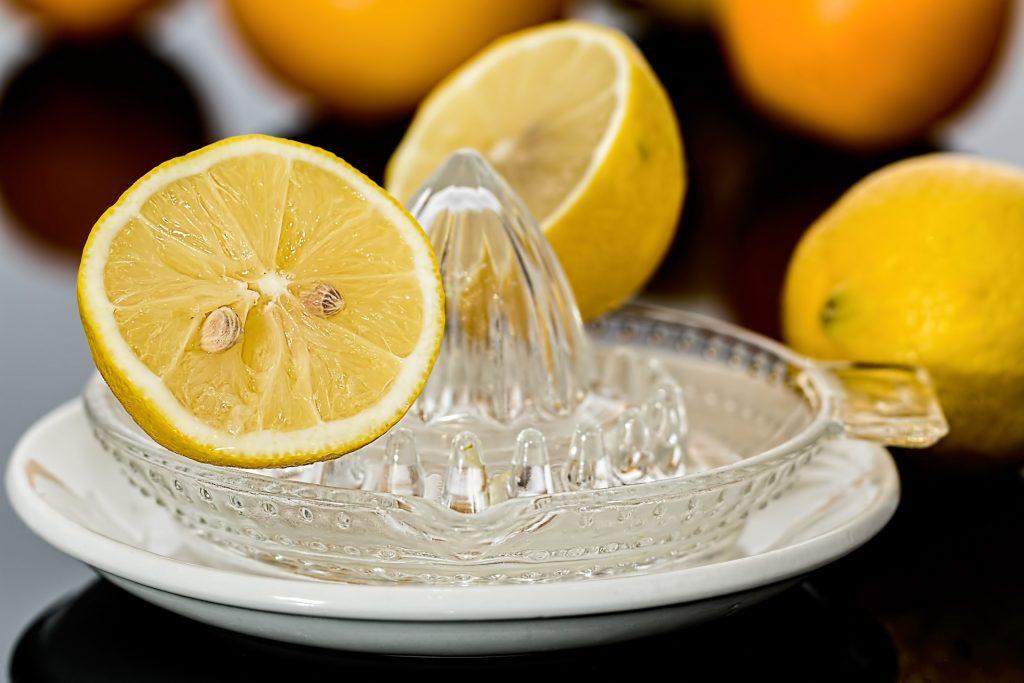 Cut lemon on glass lemon juicer.