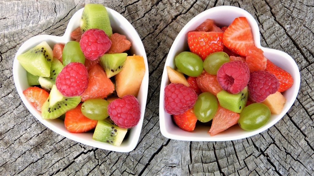 Variety of fruit in heart-shaped bowls on a wooden surface.