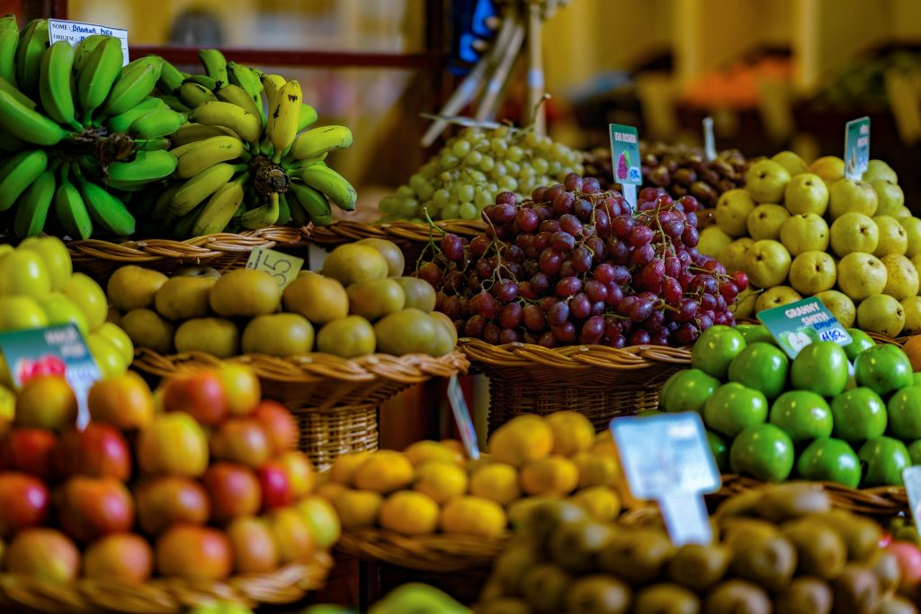 Fresh produce in baskets at a super market, including grapes, apples, bananas, pears and kiwis.
