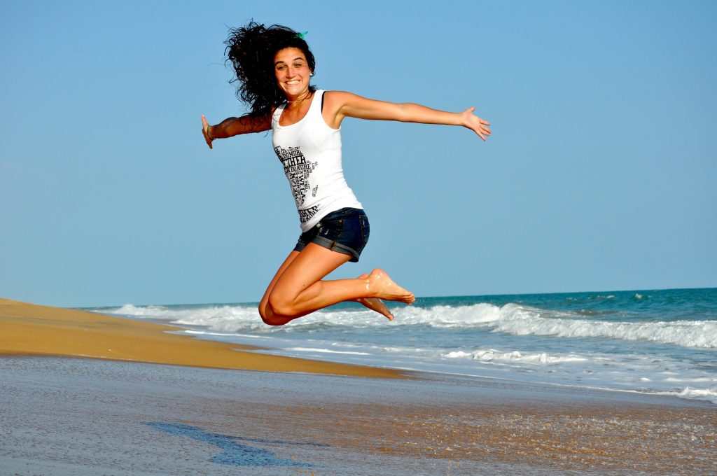 Woman jumping by the sea shore.