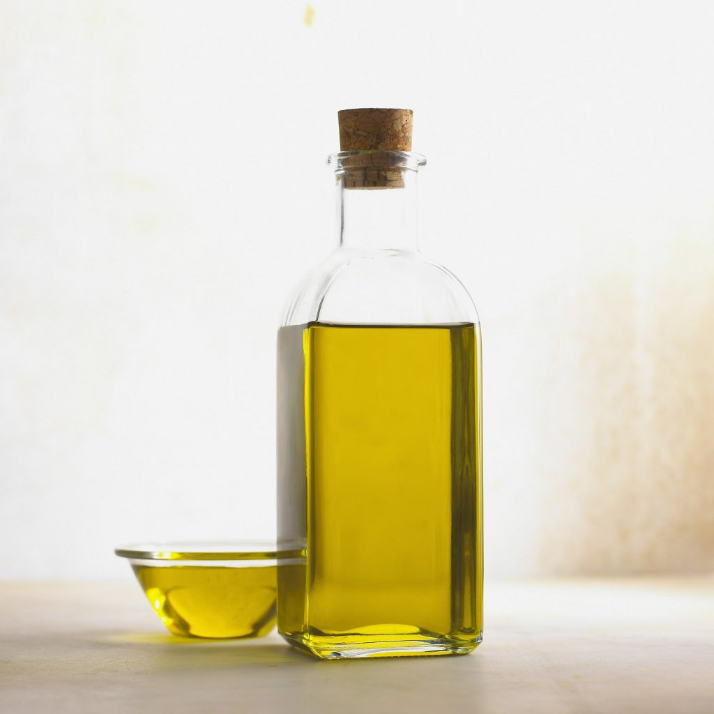 Oil in glass bottle and small glass.
