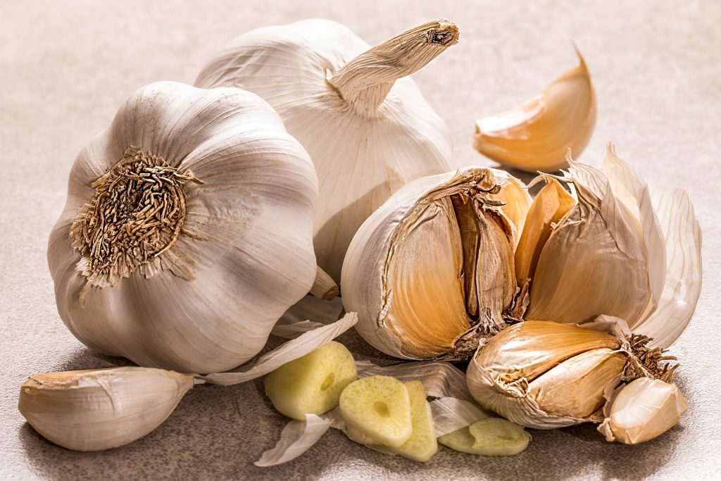 Three garlic heads on counter top, one garlic head is broken open to show cloves, one clove is broken apart to show the inside.
