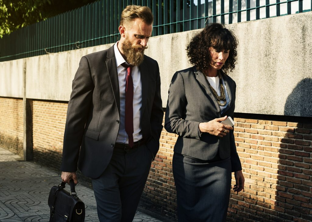 Man and woman walking in business clothing, appear to be talking.