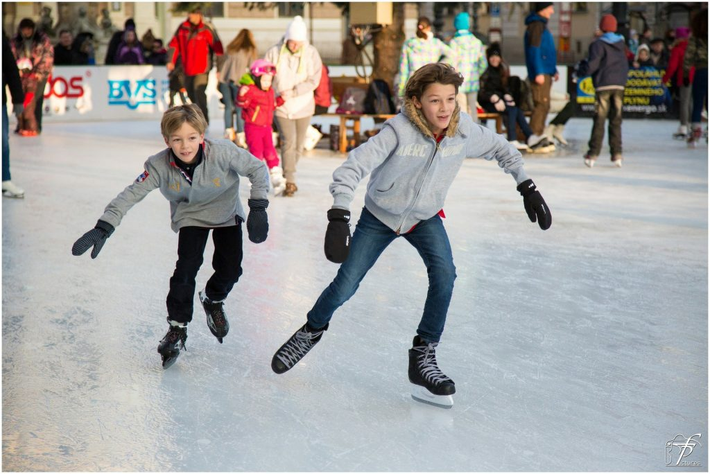 Two young boys racing on skates together at a busy skating rink.
