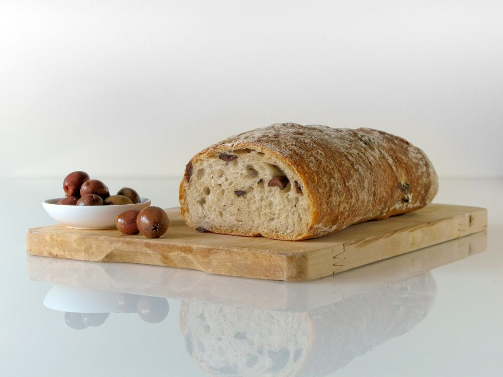 Multi-grain bread on cutting board with olives.