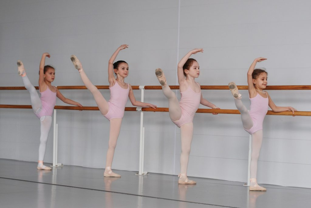 Four young girls doing ballet while holding on to bar.