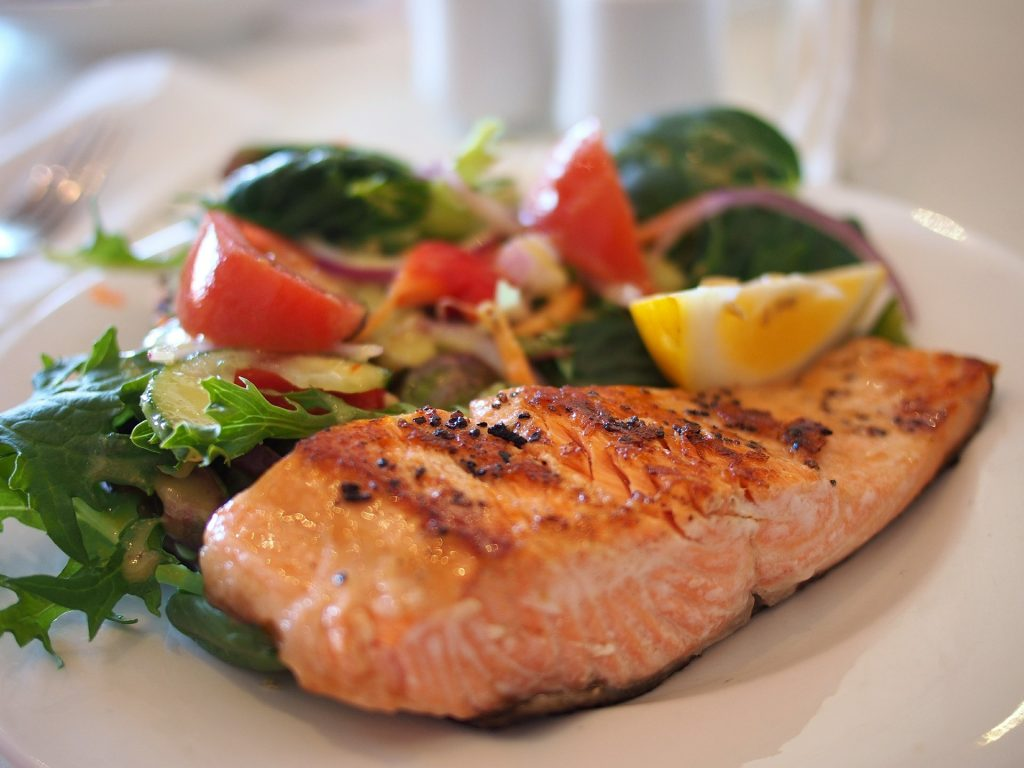 Cooked salmon dressed with lemons on a plate with a salad containing leafy greens, cucumbers, onions and tomatoes.