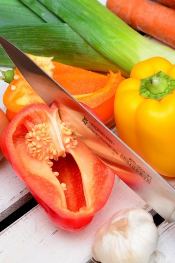 Knife cutting open a bell pepper, surrounded by a variety of vegetables on a wood table.