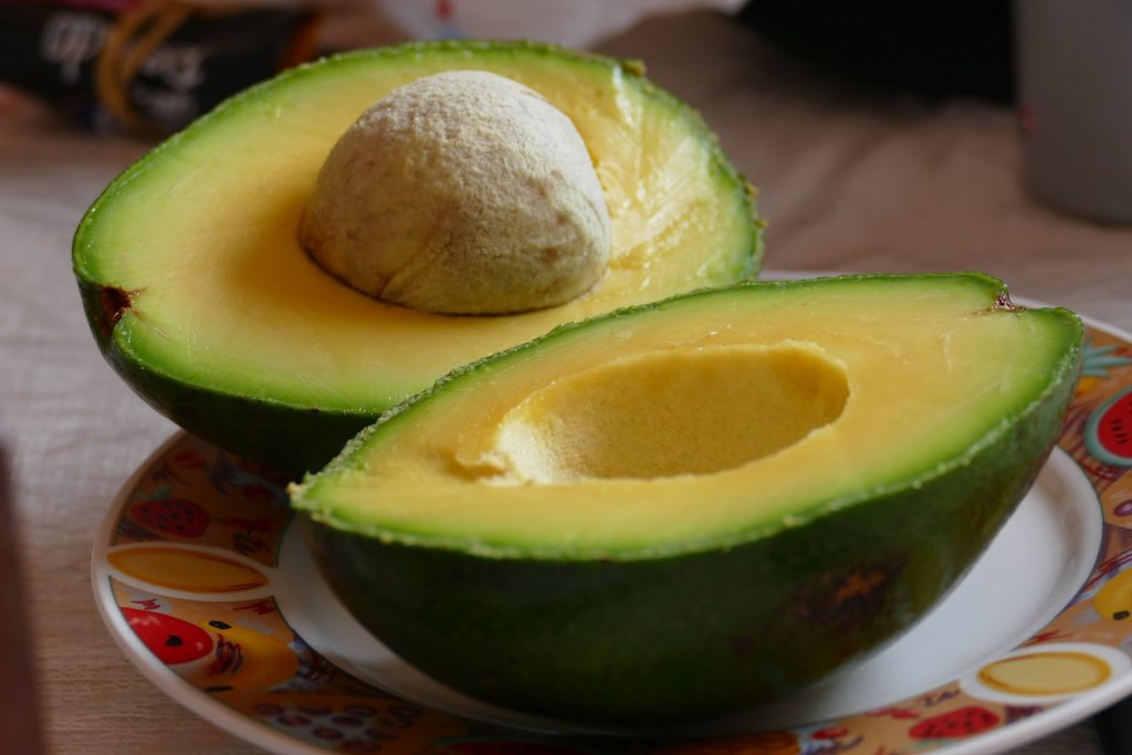 An avocado cut in half on a plate.