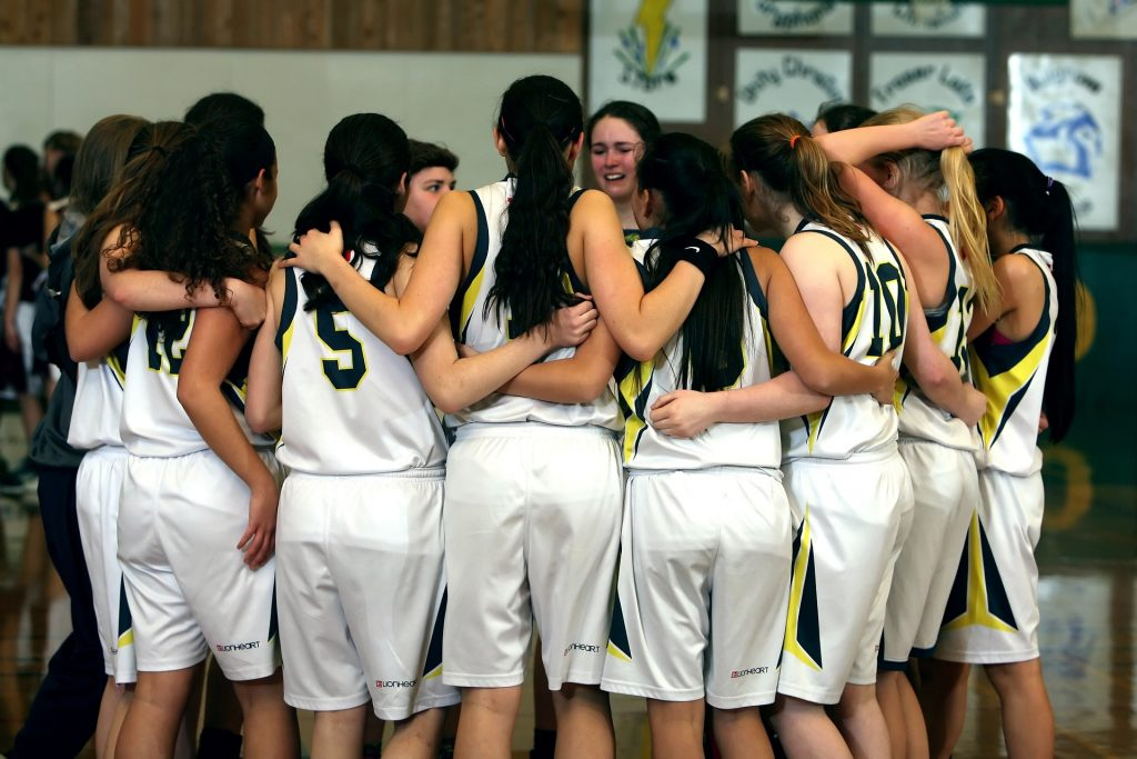 Group of female athletes in a team huddle.
