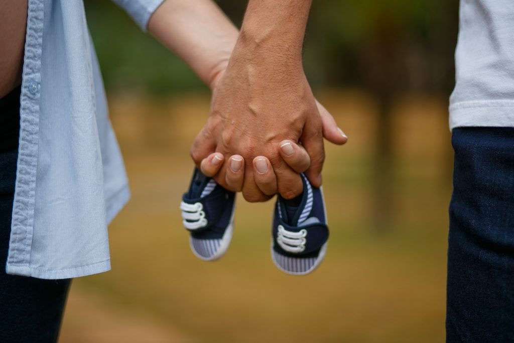 Man and woman holding hands and a small child's tennis shoes.