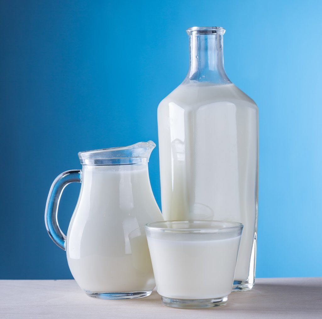 Tall bottle, small pitcher and small glass filled with milk.