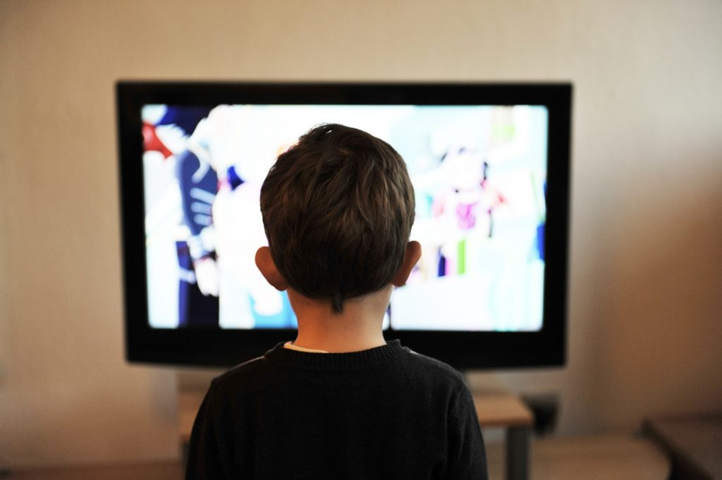 Young boy standing in front of a television.