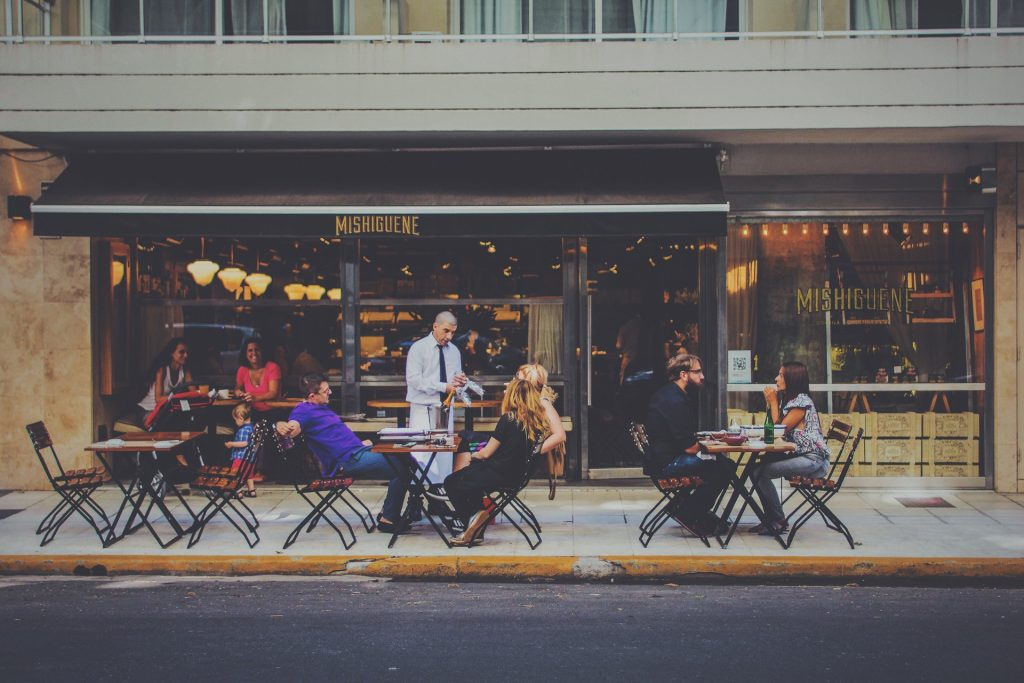 Outside of a restaurant, where three families are eating at outdoor tables.