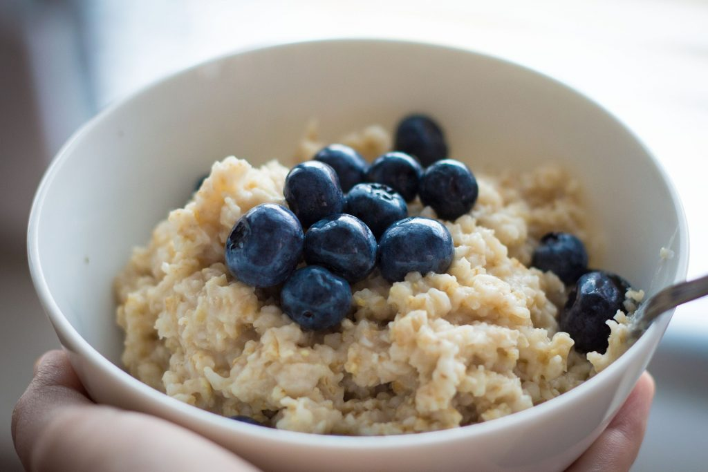 Cooked oatmeal in bowl with fresh blueberries.