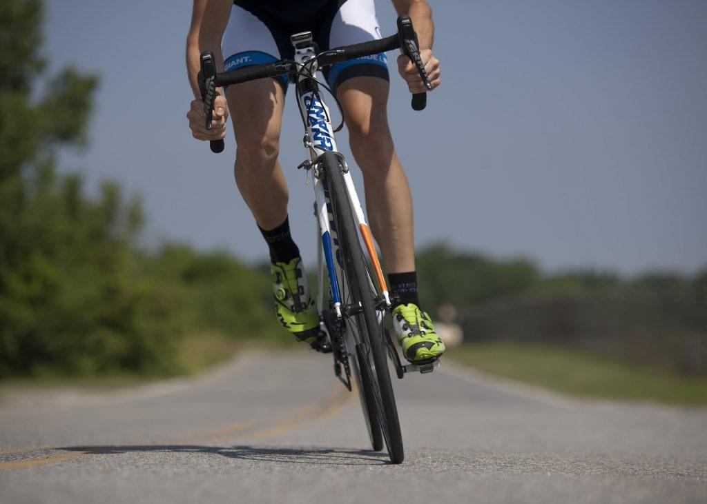 Woman biking uphill on road.