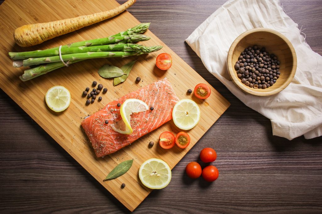 Cutting board with raw salmon, lemon, cut tomatoes, pepper, spices, asparagus and a parsnip.