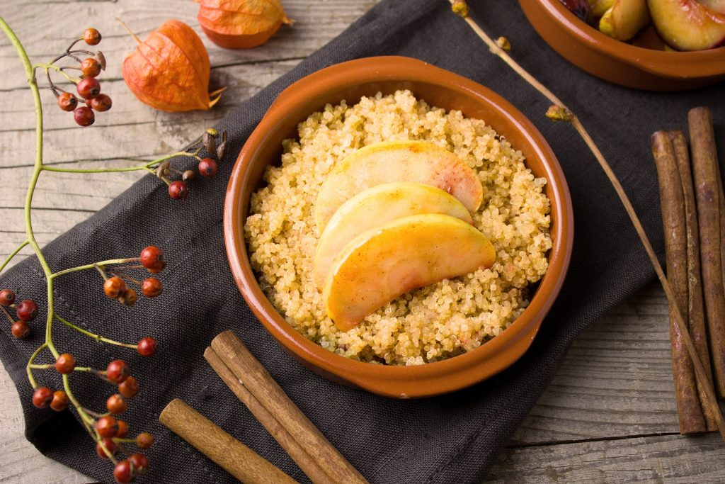 Cooked quinoa in bowl with cooked apples and spices.