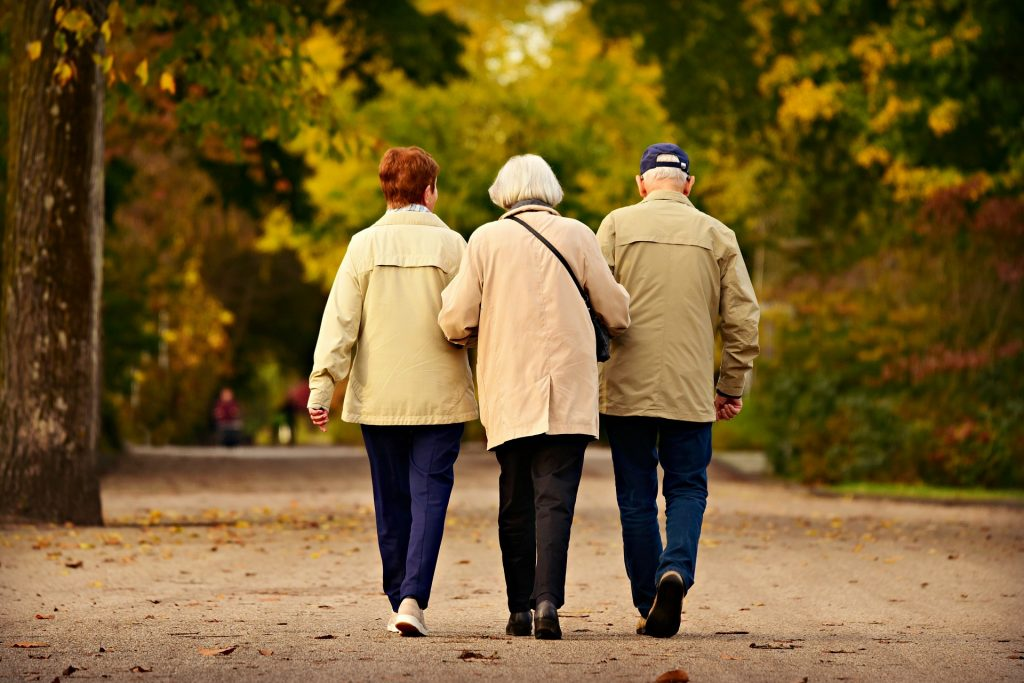 Three older adults walking together on a paved path during the fall.
