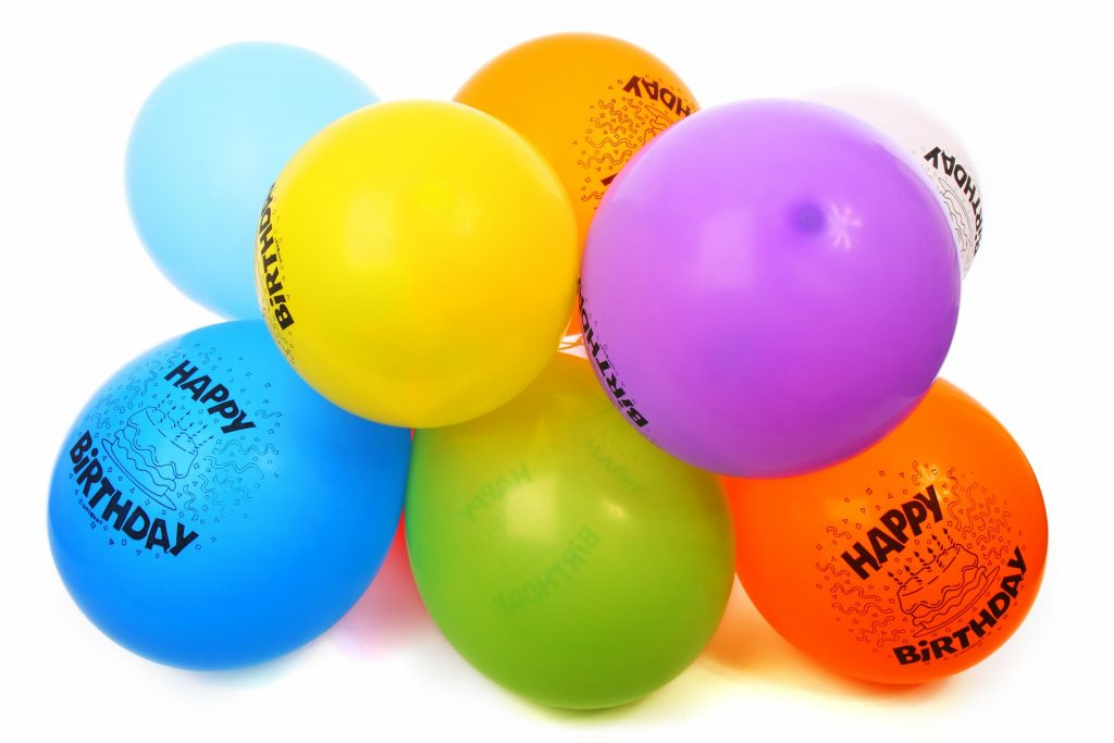 """Balloons of different colors in a bunch that read """"happy birthday""""."""