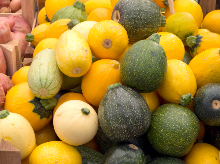 Green, yellow and white squash stacked together in a produce bin.
