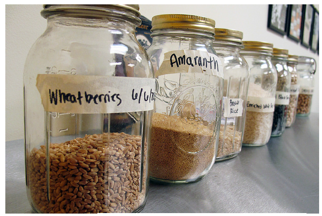 "Jars filled with whole grains, labeled ""wheatberries"", ""amaranth"" and ""brown rice""."