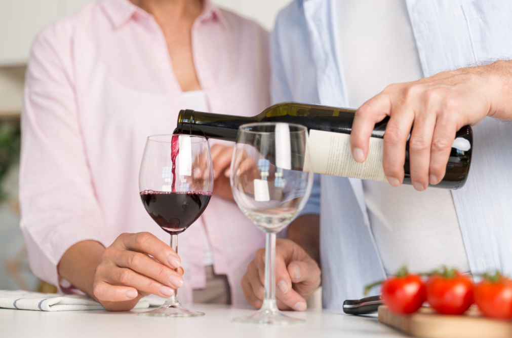 Man standing at kitchen counter pouring woman a glass of wine