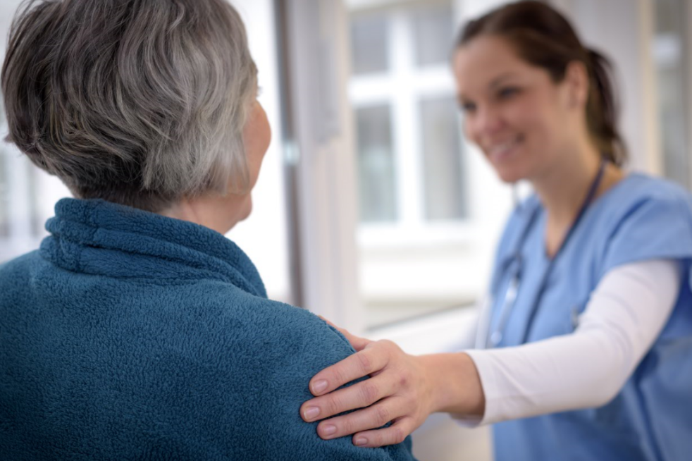 Female nurse touching the shoulder of an older woman in reassurance.