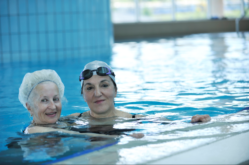 Younger woman and older woman in pool holding on to flotation device.