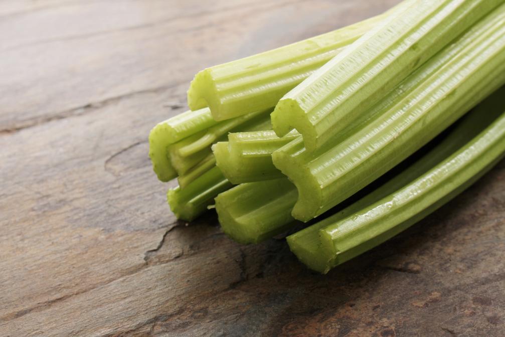 Cut celery on a wood cutting board.