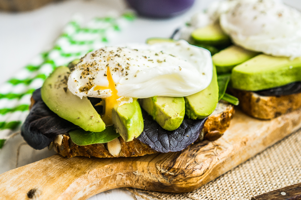 Cooked egg on top of toast with salad greens and avocado.