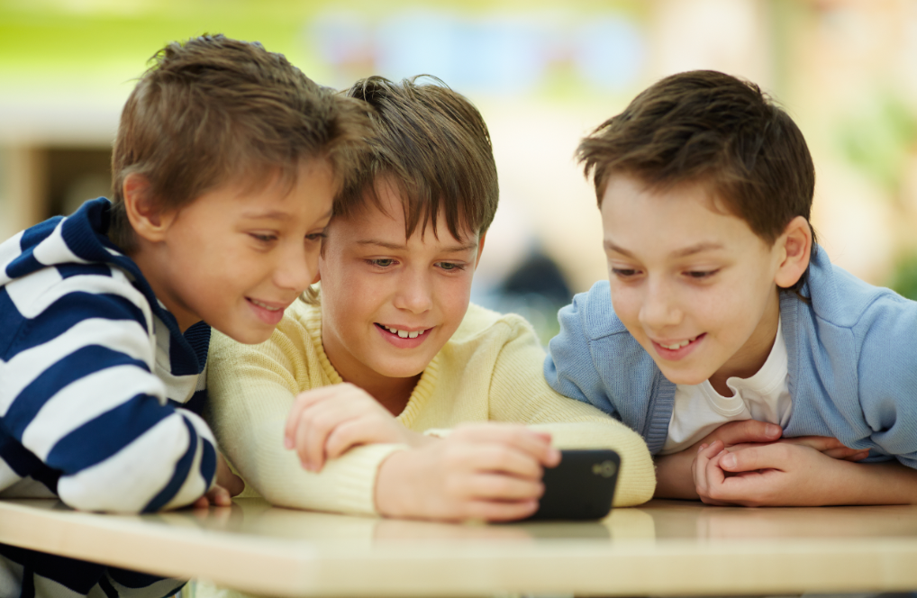 Three young boys looking at phone together at a table.