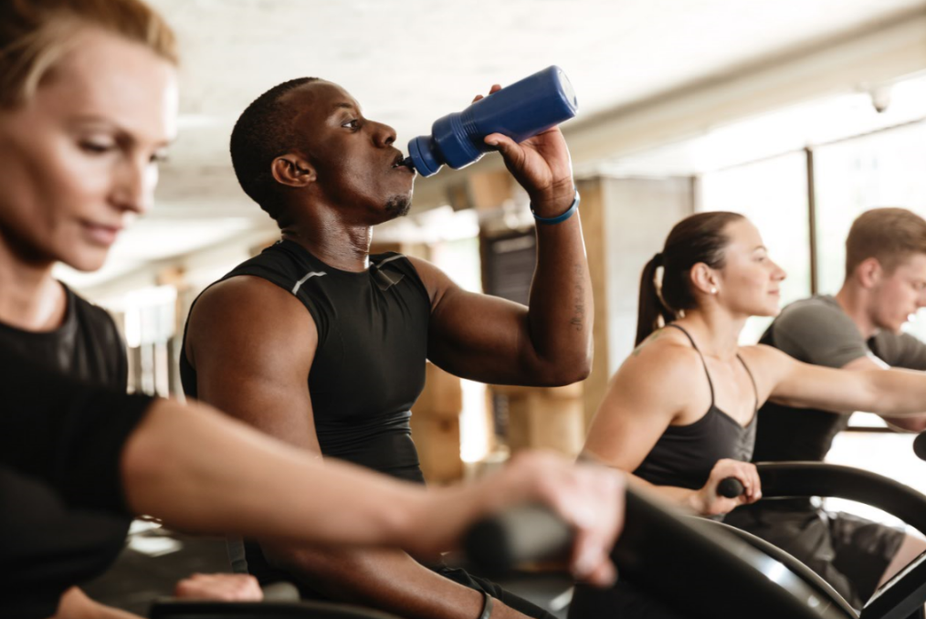 Man sitting on exercise machine drinking out of water bottle, surrounded by three more adults exercising on similar machines.