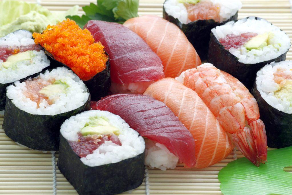 Sushi and sashimi rolls on a bamboo board.