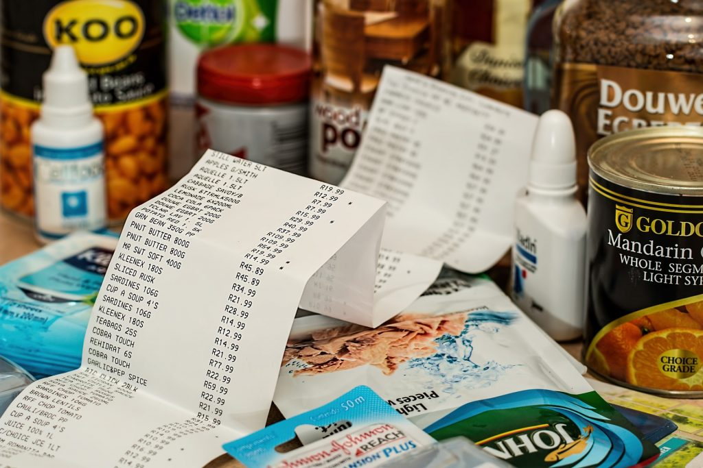 Long shopping list on top of grocery items, such as tuna, canned fruits, coffee and seeds.