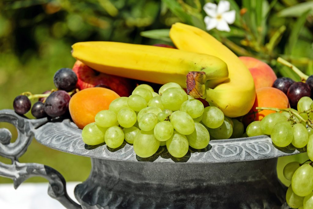 Basket of fruit, including green grapes, bananas, peaches, apples, red grapes and apricots.