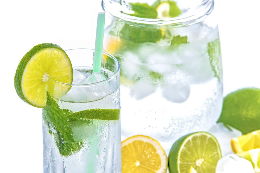 Glass of water with citrus and herbs, pitcher of water and citrus herbs in background.